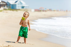 Boy at the beach with candy stock photography