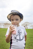 Boy on the beach drinking cocktail stock image