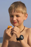 Boy on the Beach Eating Plum. Portrait of a ten years old blond boy on the beach near the sea eating plum royalty free stock image