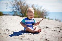 Boy on the beach. Happy boy on the sand beach with branch on sun day Stock Photos
