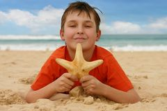 Boy on beach holding a sea star Royalty Free Stock Image