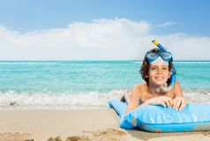 Boy on beach with inflatable matrass in scuba mask. Boy on the beach lay on inflatable blue matrass wearing scuba mask with sea waves on background royalty free stock photography