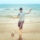 Boy on  beach kiking the football Royalty Free Stock Photo