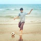 Boy on  beach kiking the football Royalty Free Stock Photo