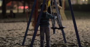 Child having fun with empty swings on playground in the evening stock video