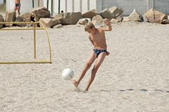Boy on beach plays football... Stock Images