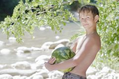 Boy in beach shade holding big green watermelon. Outdoors Stock Images