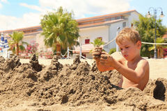 Boy on beach sits and models hills from sand. Boy on beach sits and models hills from wet sand Royalty Free Stock Image