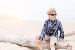 Boy at the beach. Smiling positive boy in sunglasses enjoying warm weather at the beach in california, lens flare Royalty Free Stock Photography