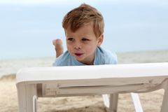 Boy on beach sunbed royalty free stock photography