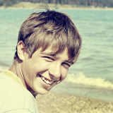 Boy at the Beach. Toned Photo of Cheerful Teenager at the Beach Royalty Free Stock Images