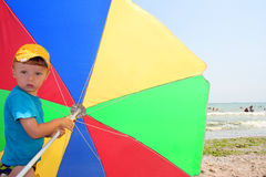 Boy with beach umbrella Stock Image