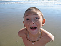 Boy at the Beach: Wide Angle Headshot. A young boy looks up at the camera and makes a goofy grin Royalty Free Stock Photos