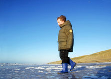 Boy at Beach in Winter. Boy in winterclothing at the beach Royalty Free Stock Image