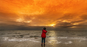 Boy on the beach in Winter. Young boy on the beach in winter. He is holding a shovel and is looking into the sea. The sky is flame red and there is light cloud stock image