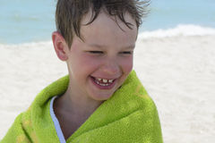 The boy on the beach wrapped in a towel, wet after swimming, Stock Photos