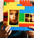 Boy and bearded man play together. Family game and childhood. Boy and bearded men play together. Dad and kid hide behind building wall made of plastic blocks royalty free stock photography