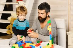 Boy and bearded man play together. Father and son. Boy and bearded men play together. Father and son with serious faces create colorful toy out of bricks. Dad stock photo