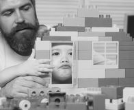 Boy and bearded man play together. Parenthood concept. Father and son make grimaces looking through door of construction. Boy and bearded men play together stock photo