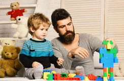 Boy and bearded man play together on wooden background. Boy and bearded men play together on wooden background. Father and son with busy faces create colorful stock photo