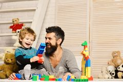 Boy and bearded man play together on wooden wall background. Family and childhood concept. Boy and bearded men play together on wooden wall background. Father stock photos