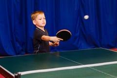 Boy beats kick in table tennis royalty free stock image