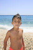 Boy with beautiful green eyes on the beach stock photo