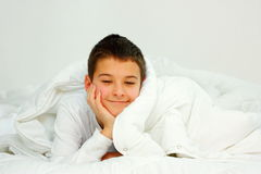 Boy in bed. A smiling boy laying on a bed covered with white blanket Royalty Free Stock Photo