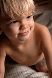 Boy on bed. Little Boy sitting on a bed with a content, soft, smiling look on his face stock images