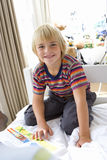Boy (6-8) on bed with book, smiling, portrait Royalty Free Stock Photos