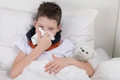 The boy is in bed, his throat hurts, he blows his nose into a paper disposable handkerchief royalty free stock images