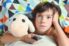 Boy in bed watch tv with remote control Royalty Free Stock Photo