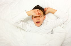 Boy in bed yawn. A boy yawning, laying in a bed covered with white blanket ready to sleep stock photos