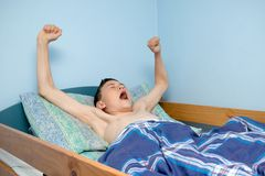 Boy in bed. Young caucasian teenage boy waking up in bed Stock Photography