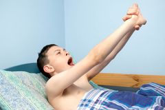 Boy in bed. Young caucasian teenage boy waking up in bed Stock Photos