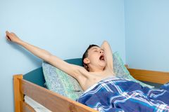 Boy in bed. Young caucasian teenage boy waking up in bed royalty free stock photos
