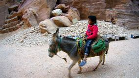 Boy beduin in red dress sit on donky. Petra. Jordan.- December. 10. 2017: :little boy beduin in red dress sit on donky in mountain canyon .jn Petra in Jordan royalty free stock images