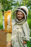 The boy beekeeper holds in his hands a honeycomb with fresh honey. Apiculture. Fresh honey. Stock Photography