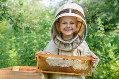 The boy beekeeper holds in his hands a honeycomb with fresh honey. Apiculture. Fresh honey. Royalty Free Stock Images