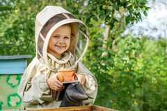Boy beekeeper Works on an apiary near a hive with a smoker in his hands. Apiculture. Royalty Free Stock Photo