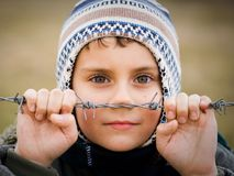 Boy behind barbed wire Stock Photos