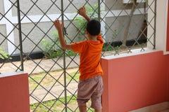 Boy behind bars stock photos
