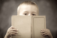 Boy behind the book. The boy hides behind the book - sepia Stock Photo