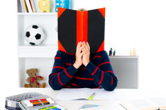 Boy behind a book Stock Photos