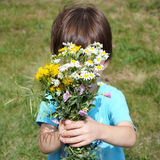 Boy behind the bouquet of wildflowers Stock Photos