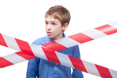 Boy behind cordon tape Stock Photo