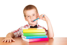 The boy behind Desk with stack of textbooks Royalty Free Stock Photo