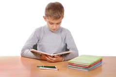 Boy behind a table reads the book Royalty Free Stock Photo