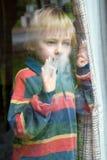 The boy behind a wet window. The little boy behind a wet window Stock Image