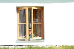 Boy behind in the window. Little boy standing behind the opened window Stock Photos